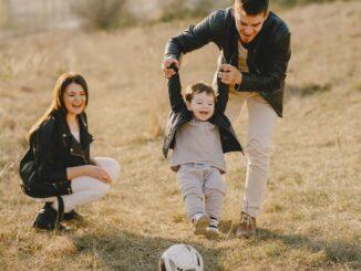 Familie leger med fodbold