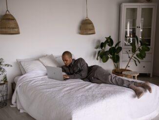Mand ligger på seng med computer